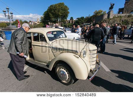 TBILISI, GEORGIA - OCT 16б 2016: Elderly man watching retro car on exhibition of vintage auto during the Tbilisoba on October 16б 2016. Tbilisoba is traditional festival in Tbilisi from 1979