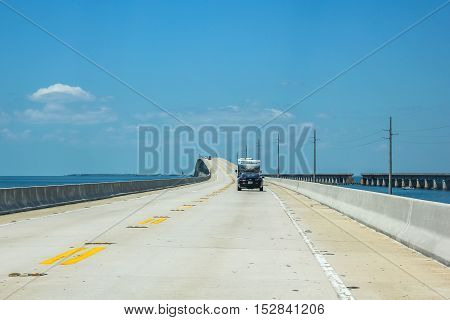 Key West, Florida, United States - April 12, 2012: cars driver on the Overseas Highway, the highway that connects the islands Keys from Florida. Alongside the Old Rail Bridge.
