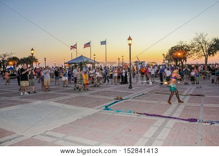 Key West, Florida, United States - April 12, 2012: fire eater walking on hot coals during the Sunset Celebration, Mallory Square. Show of street artists is one of most popular attractions of Key West.