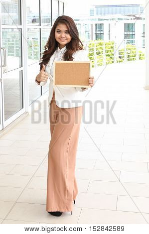 Asian young woman smile holding blank board space thumps up