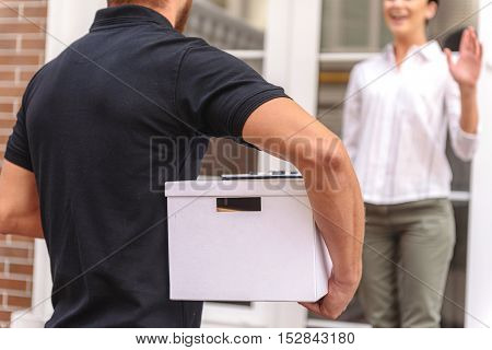 happy woman welcoming carrier with a package, selective focus
