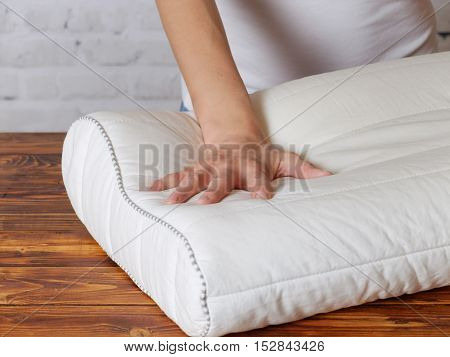 Young woman checks the stiffness of pillow