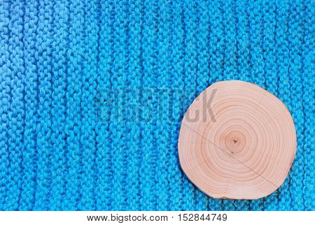 Round cut alder with annual rings on a background of blue knitted vertical rows of knitted fabric.