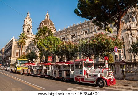 CATANIA ITALY - SEPTEMBER 13 2015: Excursion steam train in the background of the Cathedral in Catania Sicily Italy.