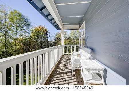 Sunny Walkout Deck With White Wicker Furniture