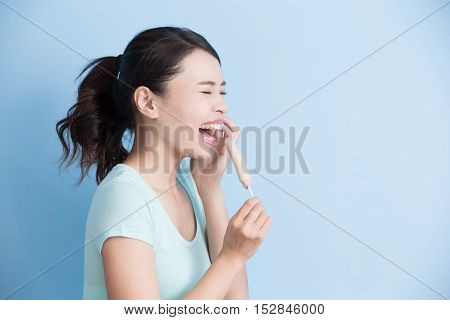 woman have sensitive teeth with ice isolatd on blue background asian