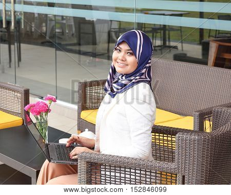 Asian Muslim woman headscarf sitting outdoor laptop smile look forward