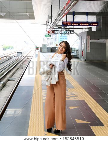 Asian young woman at train lrt station waiting time