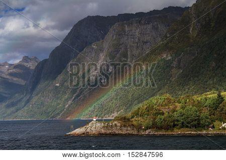 Rainbow and lighthouse at Hjorundfjord Fjordland Norway