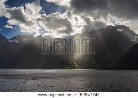 Sun beams at dramatic Hjorundfjord, Fjordland, Norway