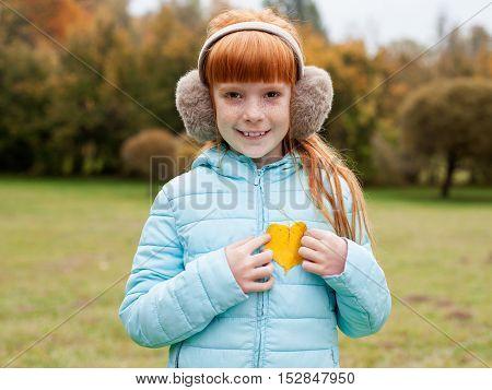 Little ginger girl in an earmuffs holding a heart shaped autumn leaf against trees