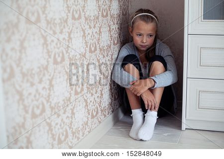 Little aggrieved girl sitting in the corner of the room