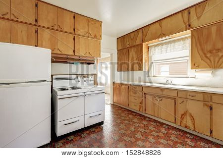 Interior of old fashioned kitchen room with linoleum floor wooden cabinets and white refrigerator and stove. Northwest USA poster