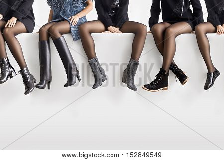 Different shoes on female feet. Woman sit on a white stairs
