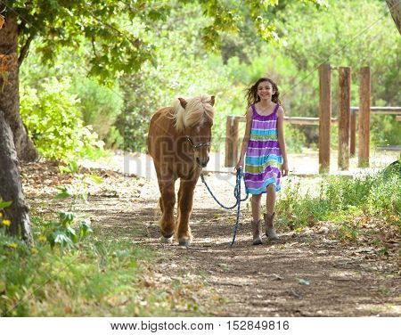 A cute little girl and her Icelandic Pony walking along a path.  They are framed by sunlight trees