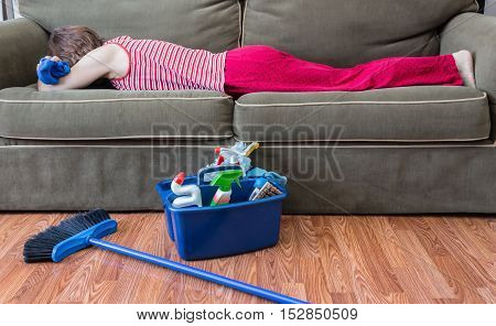 horizontal image of a house keeper sleeping on the couch with a rag in her hand and a broom and housecleaning supplies sitting on the floor next to her