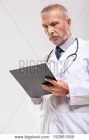 portrait of an old practitioner standing and holding the tablet