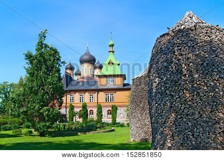 KUREMAE, IDA-VIRUMAA COUNTY, ESTONIA - AUGUST 21, 2016: Church of St Simeon and St Anna. Puhtitsa Dormition Convent. The Estonian Orthodox Church of Moscow Patriarchate. Foreground are woodpiles