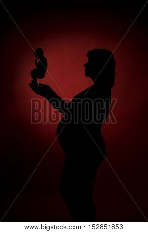 Pregnant woman holding in her hands the symbol of embryo. Abortion concept. Red background