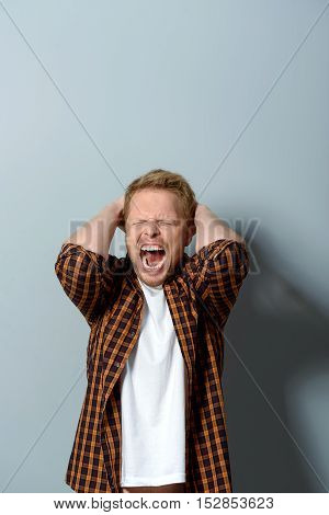 upset guy screaming and covering his ears with hands