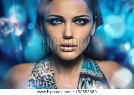 Portrait of a beautiful young woman with long hairs over bright night lights