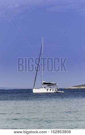 view of a sail boat at anchor over a cristal blue sea. croatia