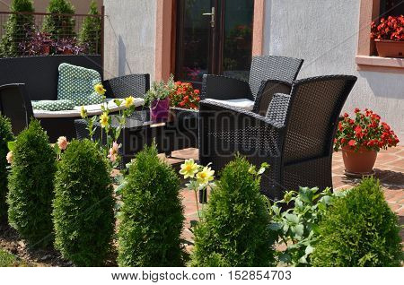 Set of garden furniture in a house back yard surrounded with bushes and flowers