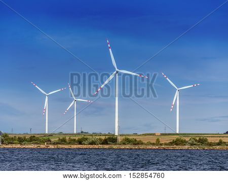 Four wind power generators against blue sky