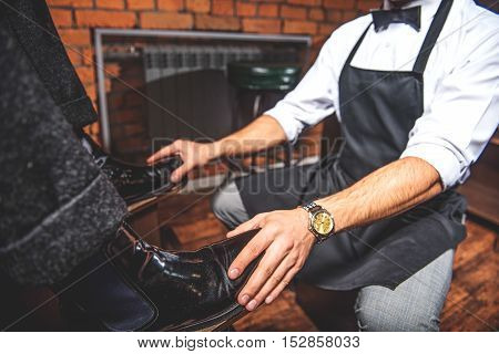 hands of a shoe shiner holding brogues on legs of the client