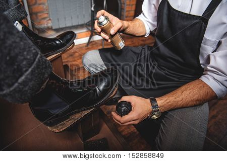 modern artificer ready to spray chemicals on the pair of footwear