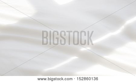 closeup of soft white bedsheets in the morning light