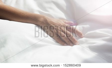 closeup of arm of a woman on white bedsheets