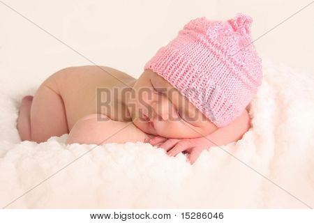 Newborn baby girl in a knitted hat.