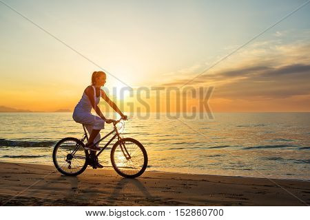Woman On Vacation Biking At Beach