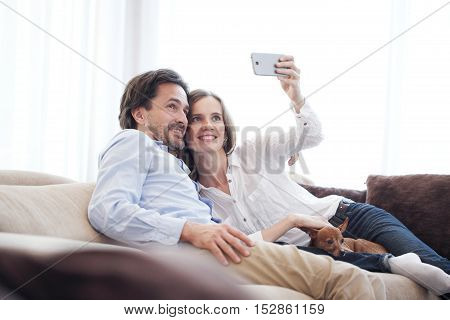 Happy couple taking a selfie together on the couch at home
