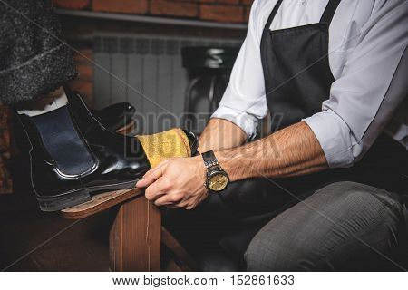 waxing brogues using a vintage shoe shine box with a polishing rag and a wooden shoe platform, side view