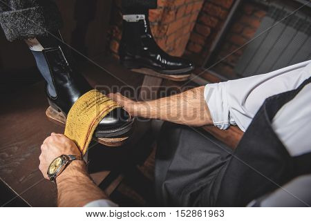 guy gets his shoes polished by a worker using polishing rag and a wooden shoe platform