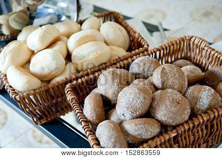 Wheat and rye bread rolls in baskets