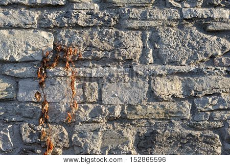 Gray pattern of old style design decorative cracked real stone wall surface with cement. Part of a stone wall, for background or texture. Antique natural stonewall background