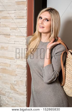 Lovely young blond female entering a room witha big bag, wearing a grey dress.