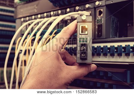 engineer connecting network cable to switch