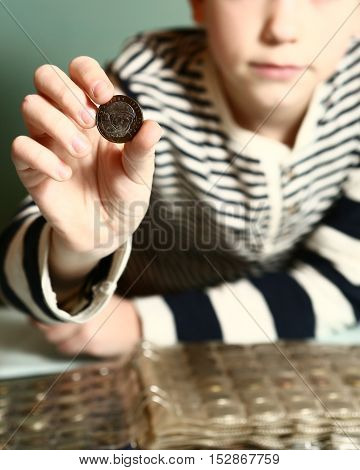 preteen handsome boy with coin collection. Boy collectioner