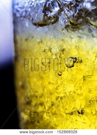 Colorful cocktail in glass with splashes and lemon on dark background. Party club entertainment. Mixed light.
