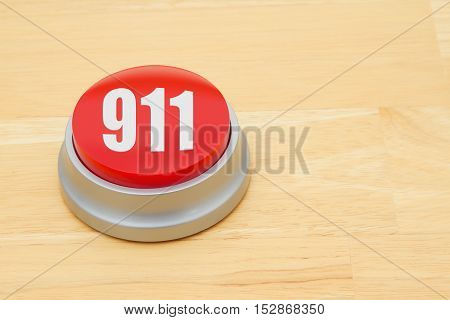 A 911 red push button A red and silver push button on a wooden desk with text 911