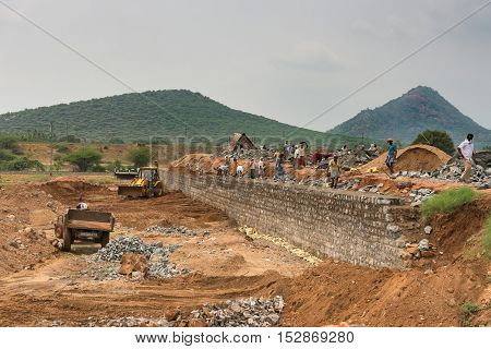 Dindigul India - October 22 2013: Large number of people build a stone dam mostly with manual labor in the Dindigul region of Tamil Nadu. A bulldozer and truck in picture. Green hill and gray sky.