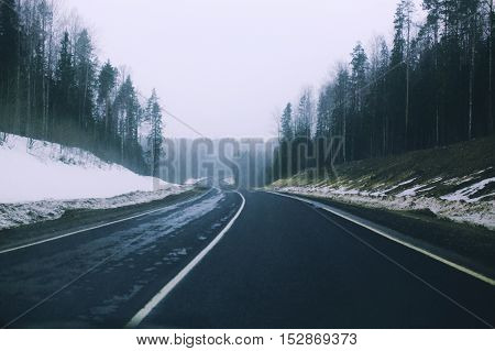border seasons. highway divides the forest into two parts. forest with snow and forest with green grass. the concept of the changing seasons