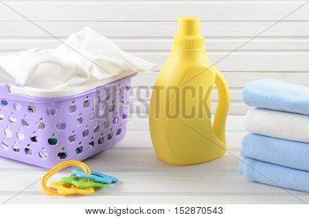 Dirty Baby Napkins In A Plastic Purple Laundry Basket, Clean Folded And Ironed Baby Swaddle, Baby To
