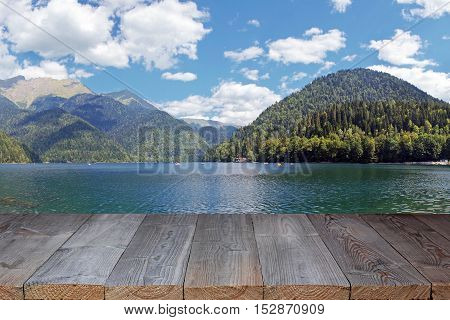 Empty wooden table against the background of a lake panorama in mountains. Panorama overlooking Rits's lake in mountains in Abkhazia in a summer sunny day. Blank space for your object.