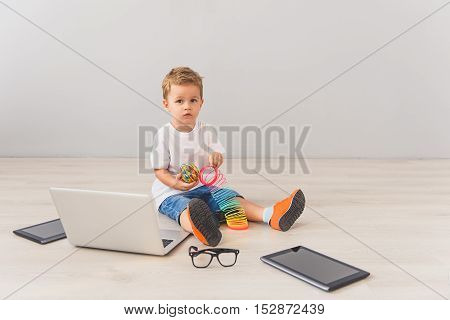 So tech savvy. Little cute boy sitting on floor in studio, posing for camera next to digital gadgets