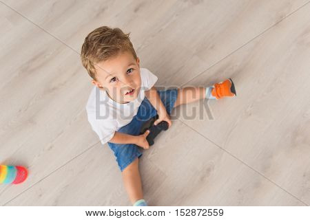 Playtime for child. Top view photo of small boy holding console in his hands and looking into camera